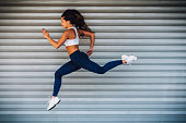 Image of young female athlete running and jumping outdoors. Copy space has been left, shoot with available light.