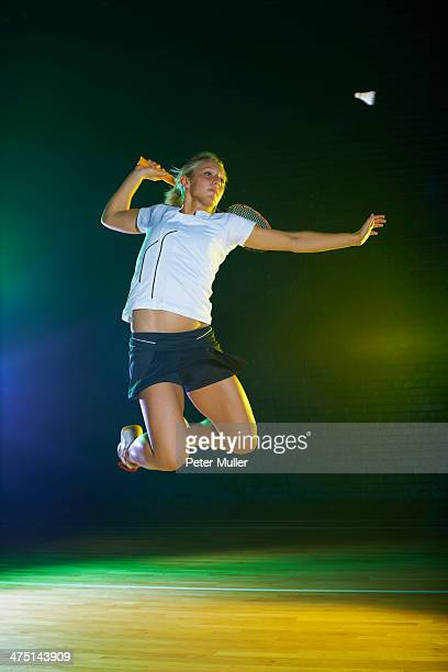 Young female badminton player mid air on court