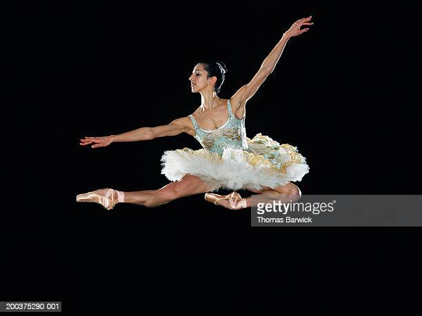 Young female ballerina jumping in midair, arms outstretched