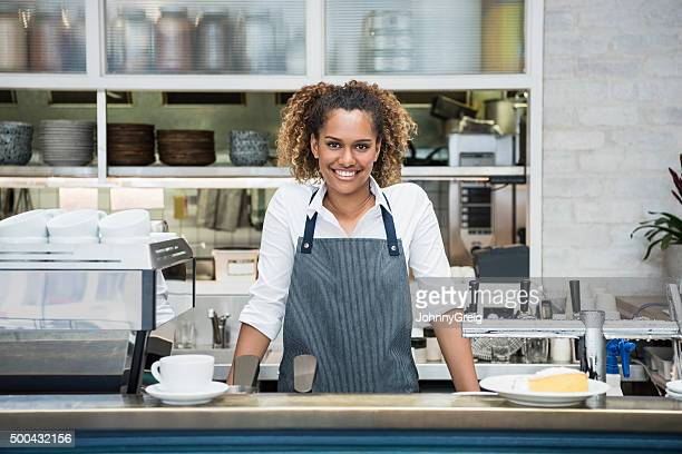 Young female barista at counter in cafe, portrait