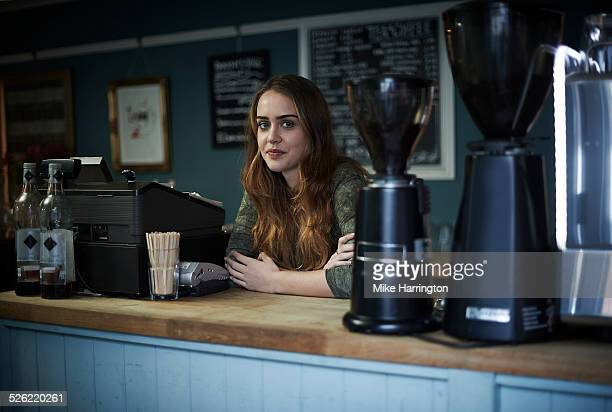 Young female barista in cafe