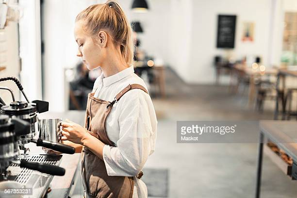 Young female barista using espresso maker at cafe
