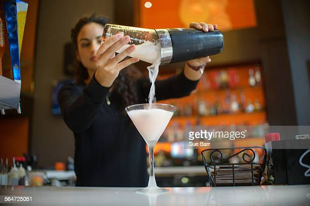 Young female bartender pouring cocktail from shaker in cocktail bar