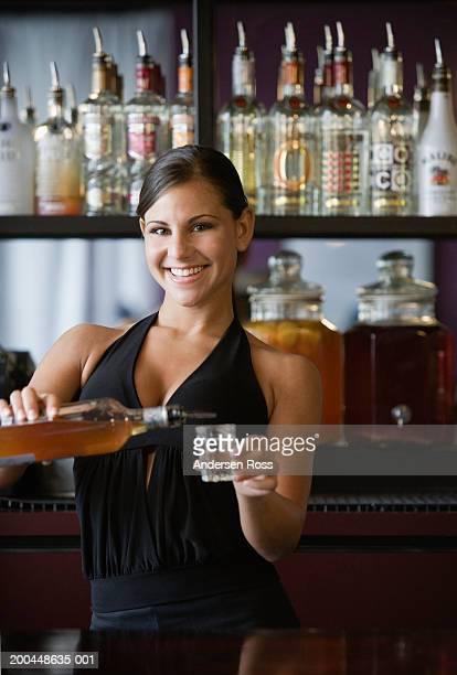 Young female bartender pouring liquor into shot glass, portrait