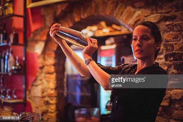 Barman jeune femme préparant Shaker à cocktail dans un bar à cocktails