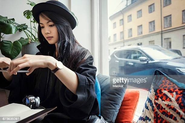 Young female blogger photographing through smart phone while sitting by window in office