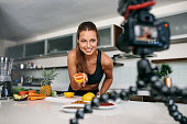 Young woman recording food based video content on camera. Woman showing a cut orange facing the camera.