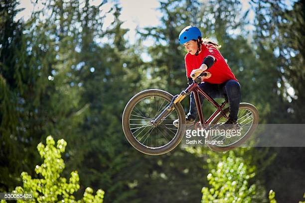 Young female bmx biker jumping mid air in forest
