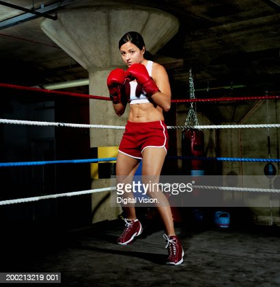 Young female boxer in ring, gloves raised, portrait