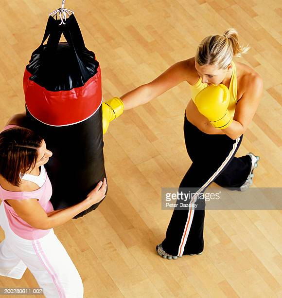 Young female boxer kicking punch bag held by young woman