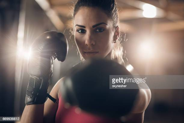 Young female boxer on a sports training in a gym.