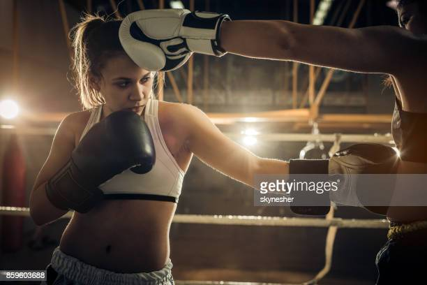 Young female boxer practicing with sparring partner in a ring.