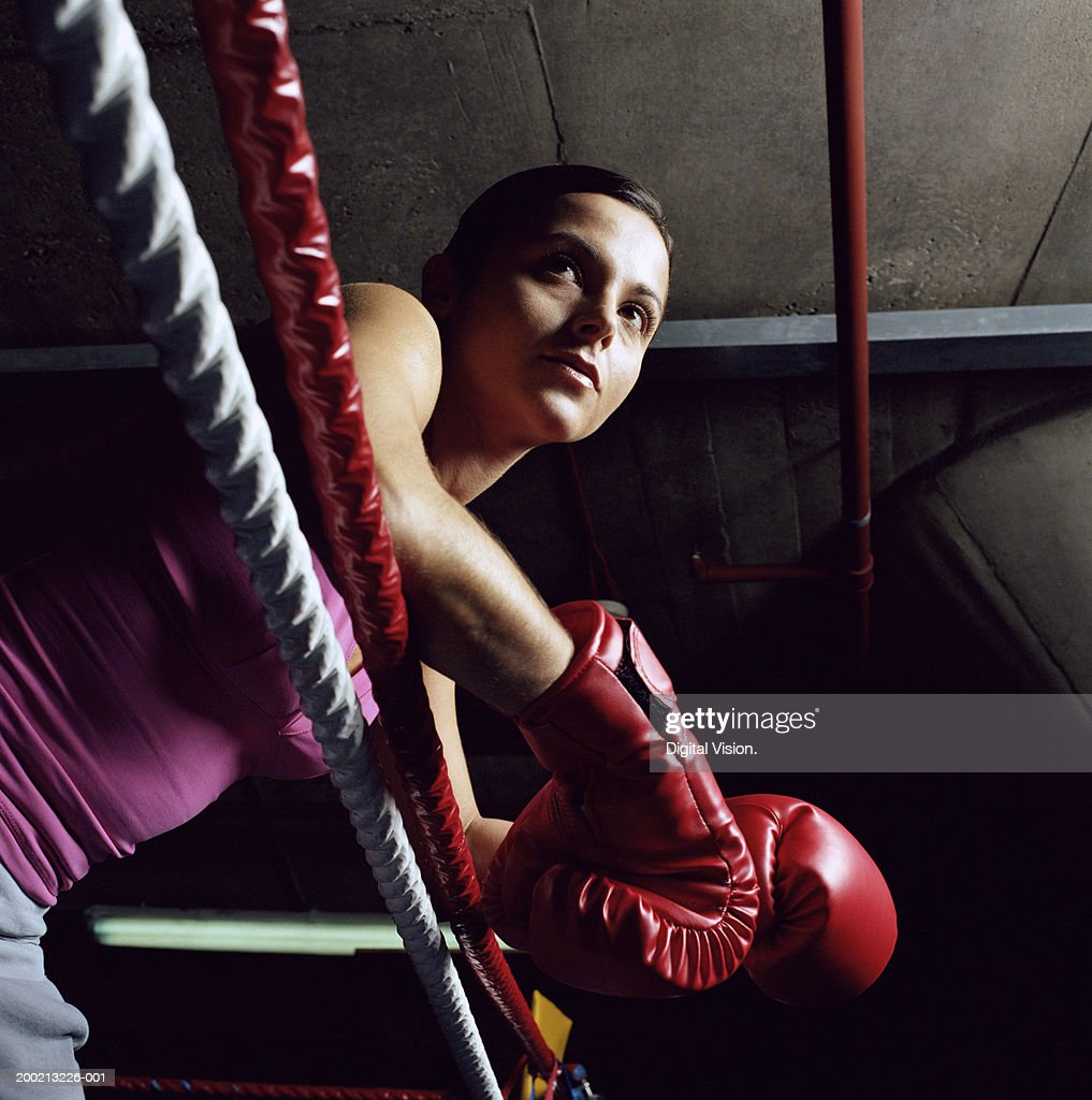 Young female boxer resting arms on ropes, low angle view