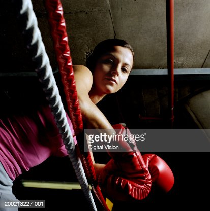 Young female boxer resting arms on ropes, portrait, low angle view