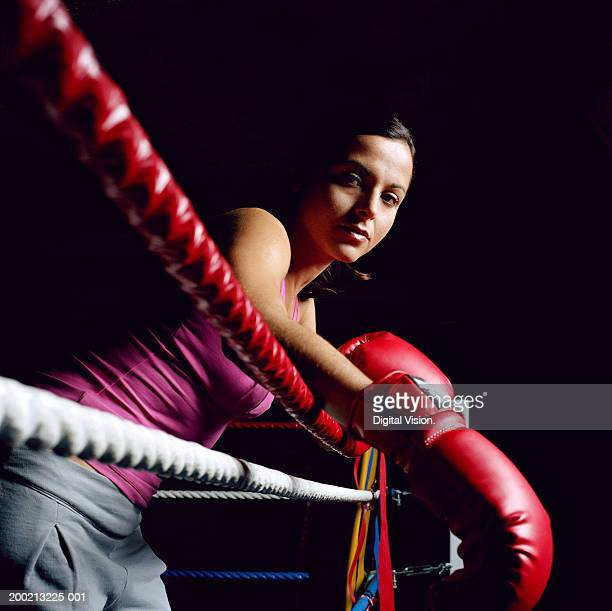 Young female boxer resting arms on ropes, portrait