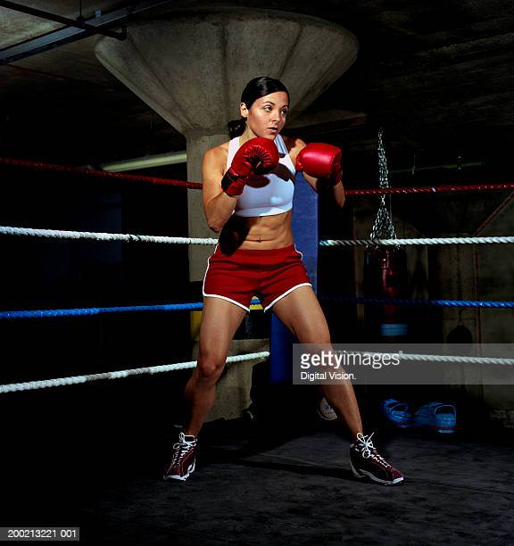 Young female boxer standing in ring with gloves raised