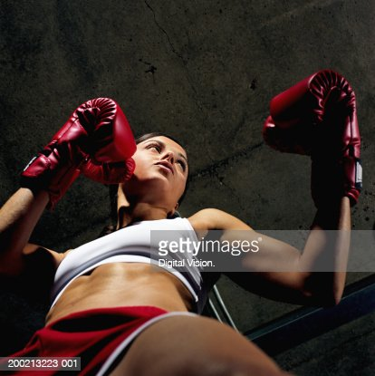 Young female boxer with gloves raised, low angle view