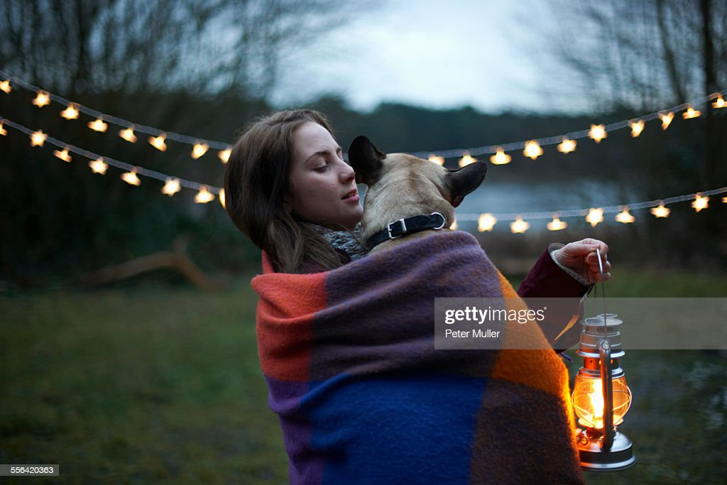 Young female camper with dog wrapped in blanket