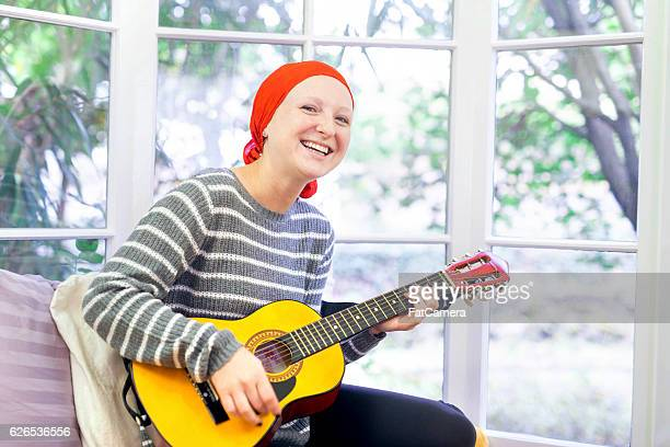 Young female cancer patient feeling happy while playing the guitar
