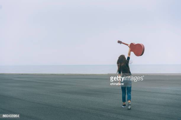 young female carrying guitar walking against sky