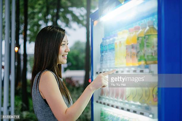 Young female choosing drinks from vending machine