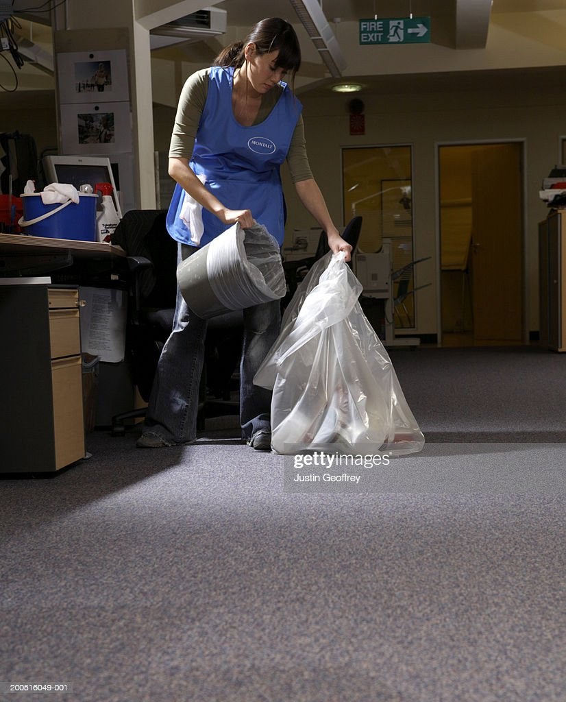 Young female cleaner emptying rubbish bin in office : Stock Photo