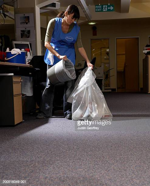 Young female cleaner emptying rubbish bin in office