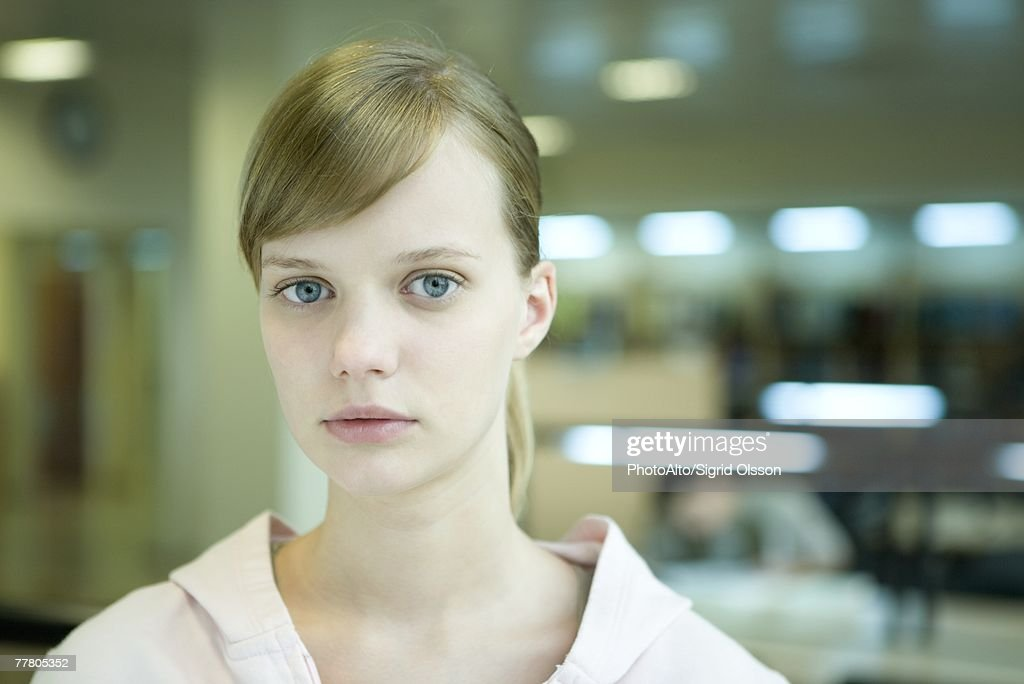 Young female college student in library, looking at camera, head and shoulders : Stock Photo