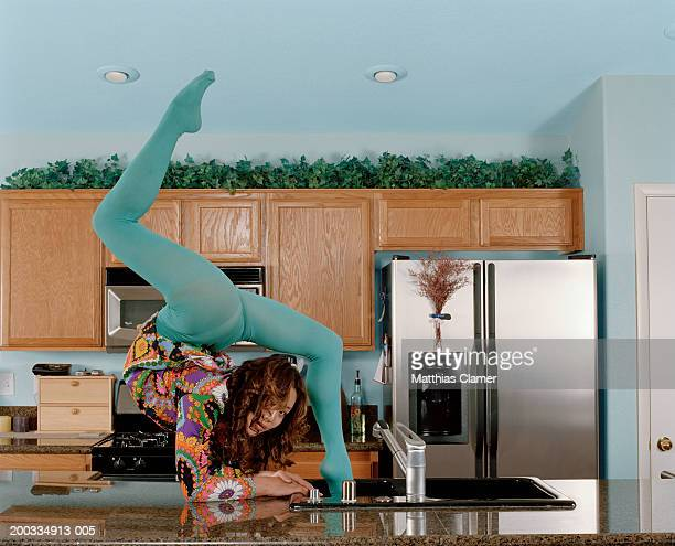 Young female contortionist bending over backwards at kitchen sink