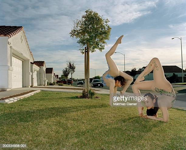 Young female contortionists bending over backwards on lawn