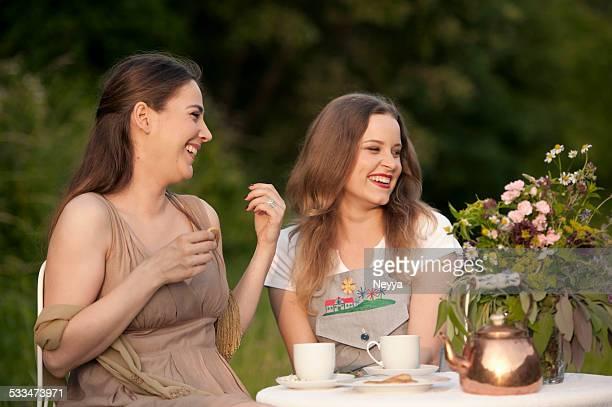 Couple jeune femme appréciant le thé de l'après-midi sur le jardin