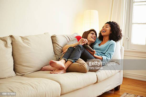 Young female couple reclining on sofa looking at digital tablet