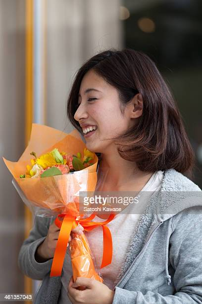 Young female deep breathing with a bouquet