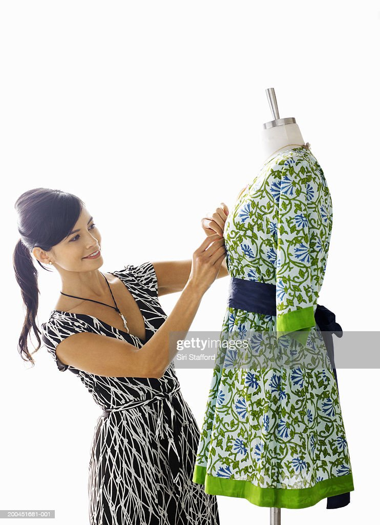 Young female designer fixing dress on mannequin form : Stock Photo