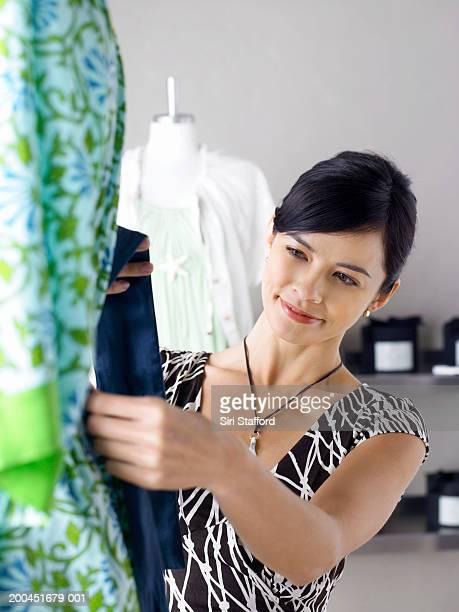 Young female designer looking at sash in boutique