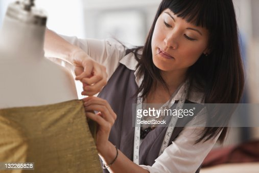 Young female designer pinning fabric to mannequin