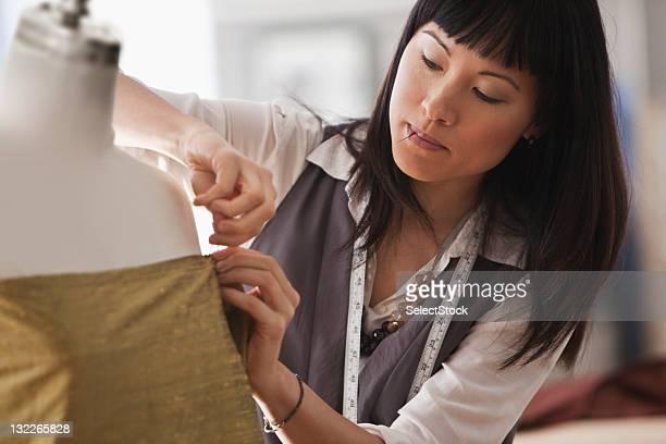 若い女性デザイナーファブリックのマネキンを刺す
