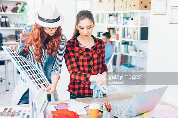 Young female designers holding a color swatch and working