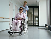 Young female doctor pushing female patient in wheelchair
