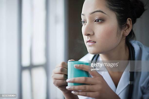 若い女性医師ており、コーヒーブレイクやを見ているの眺めをご覧いただけます。