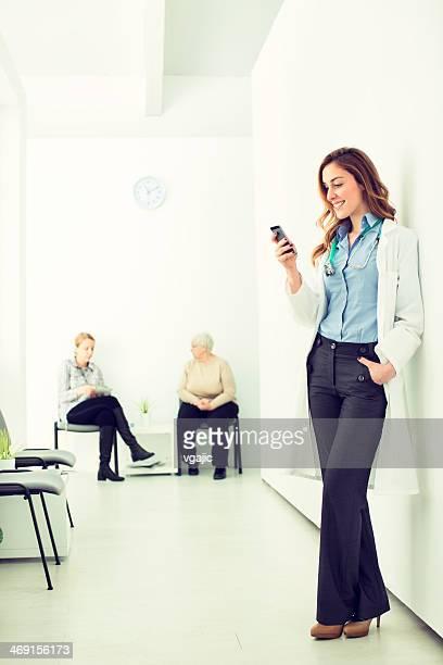 若い女性医師メールに病院の廊下。