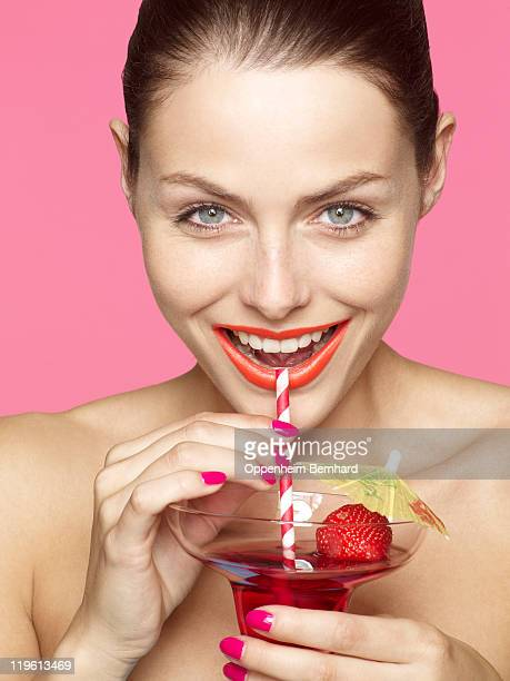 young female drinking cocktail and laughing