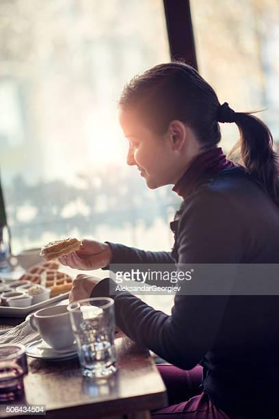 Giovane donna mangiando cialde per la prima colazione al ristorante