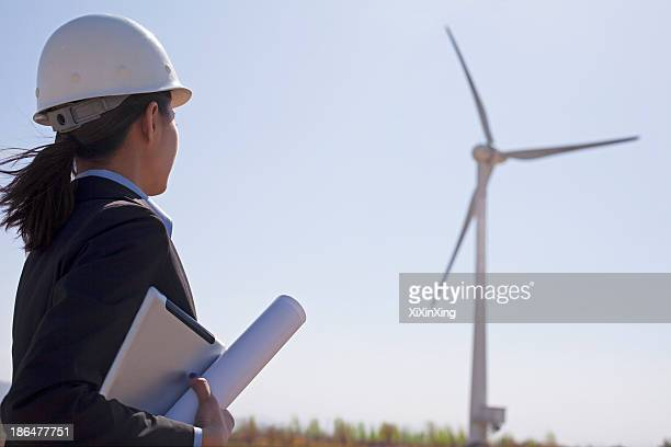Young female engineer holding blueprints and checking wind turbines on site,