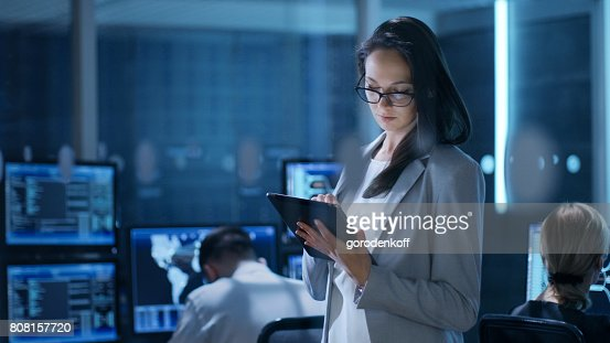 Young Female Engineer Uses Tablet in System Control Center. In the Background Her Coworkers are at Their Workspaces with many Displays Showing Valuable Data. : Stock Photo