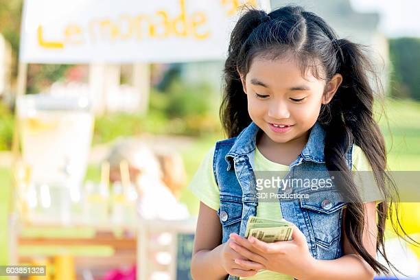 Young female entrepreneur counts lemonade profits