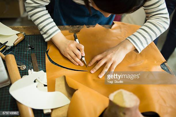 Young female entrepreneur in her shoe making studio