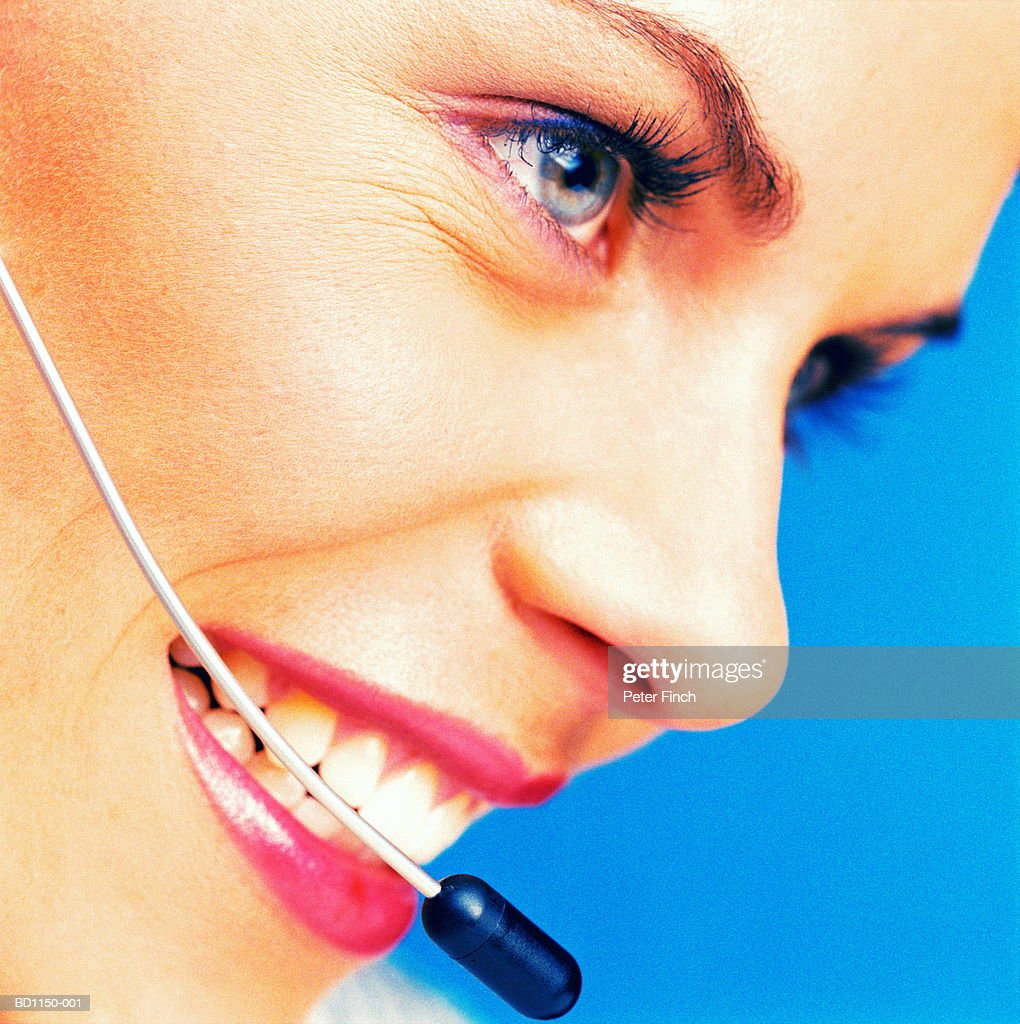 Young female executive wearing telephone headset, close-up : Stock Photo