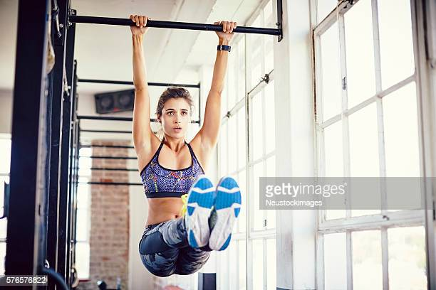 Young female exercising on pull-up bar in gym