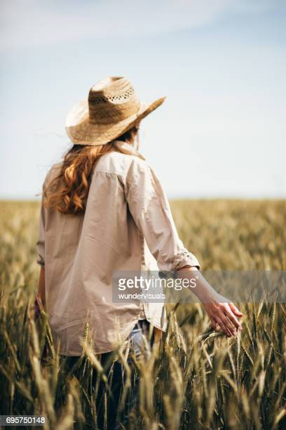 Young female farmer standing in a field of organic wheat